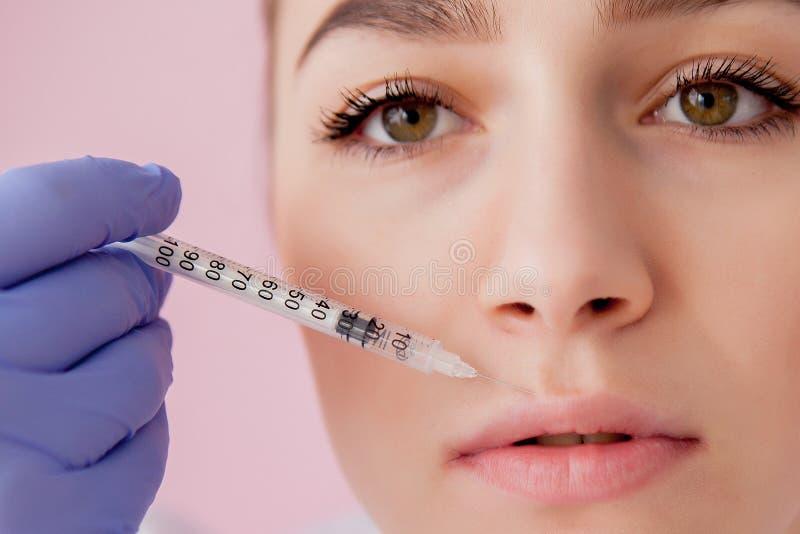 Doctor in de handschoenen die een vrouw botox injecteert in lippen, op roze achtergrond stock afbeeldingen