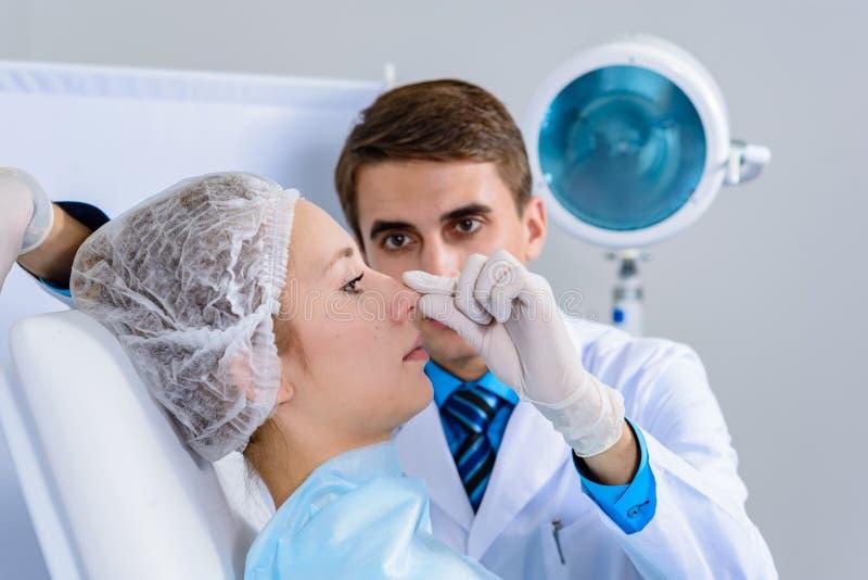 Doctor de la cirugía plástica, inspección paciente y consulta foto de archivo libre de regalías