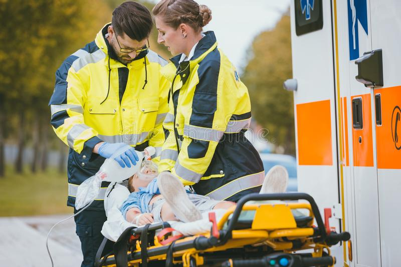Doctor de la emergencia que da el oxígeno a la víctima del accidente imagenes de archivo