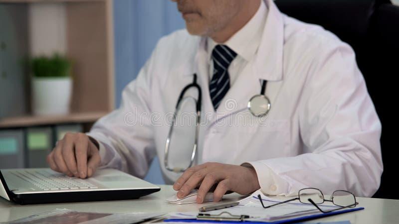 Doctor de la medicina que escribe el artículo científico para la revista, trabajando en el ordenador portátil imagen de archivo libre de regalías