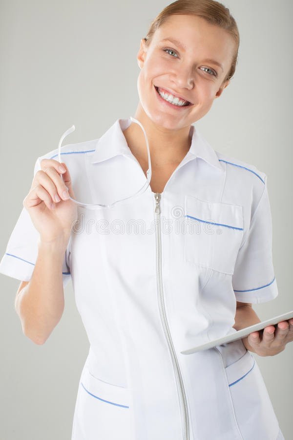 Doctor de la mujer con el estetoscopio que sostiene los vidrios y la tableta electrónica foto de archivo libre de regalías