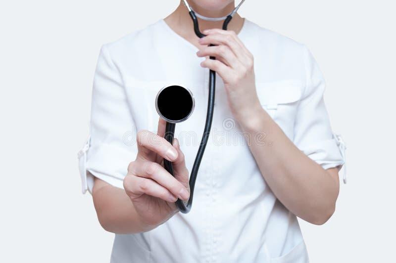 Doctor de la mujer con un estetoscopio en manos en el fondo blanco aislante imagen de archivo libre de regalías