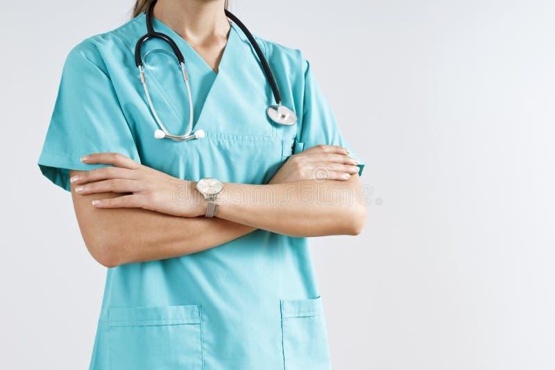 Doctor de la mujer en la situación uniforme azul con los brazos cruzados, aislados fotos de archivo libres de regalías