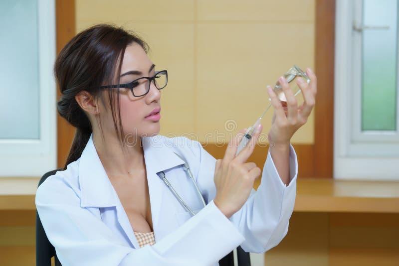 Doctor de la mujer joven que prepara la inyección con la ampolla y la jeringuilla imágenes de archivo libres de regalías