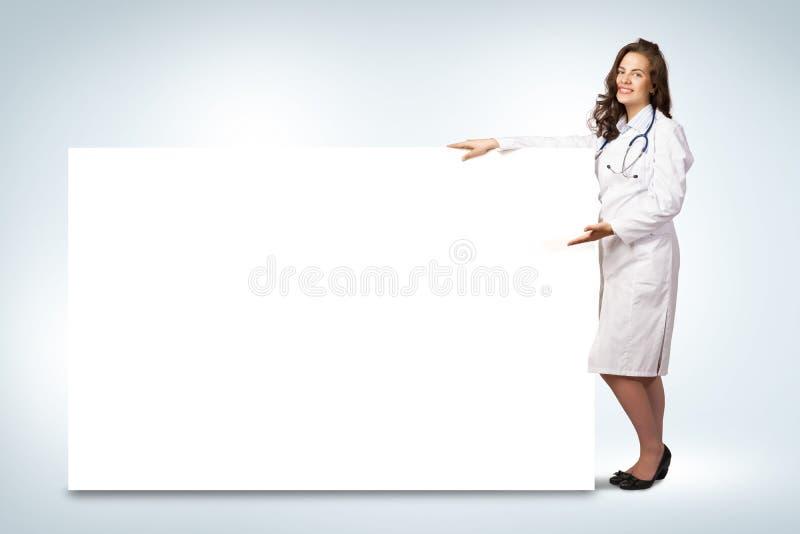 Doctor de la mujer joven que se coloca cerca de una bandera en blanco fotografía de archivo libre de regalías