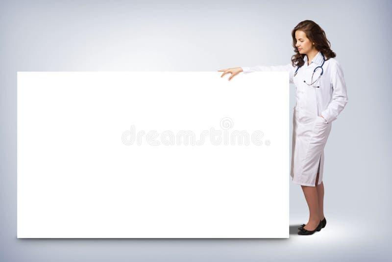 Doctor de la mujer joven que se coloca cerca de una bandera en blanco foto de archivo libre de regalías