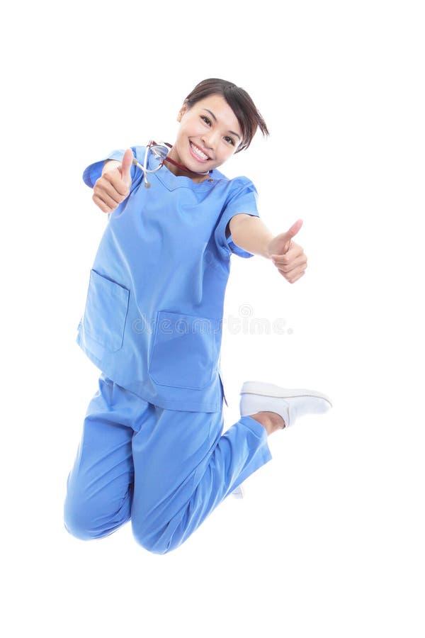 Doctor de la mujer que salta con el pulgar para arriba fotografía de archivo
