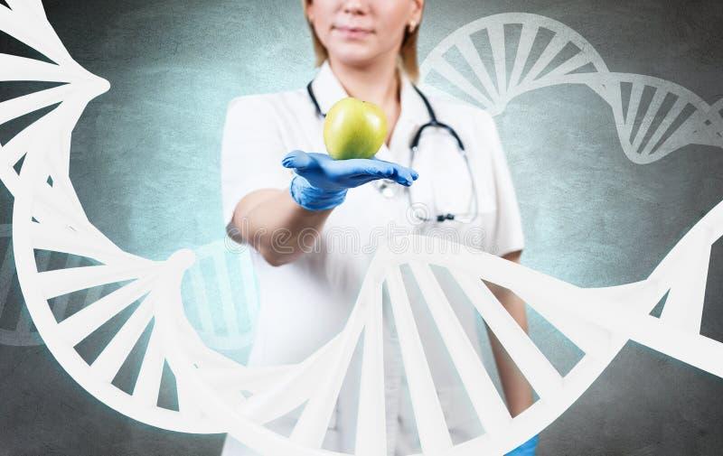 Doctor de la mujer que se coloca entre cadena grande de la DNA foto de archivo libre de regalías