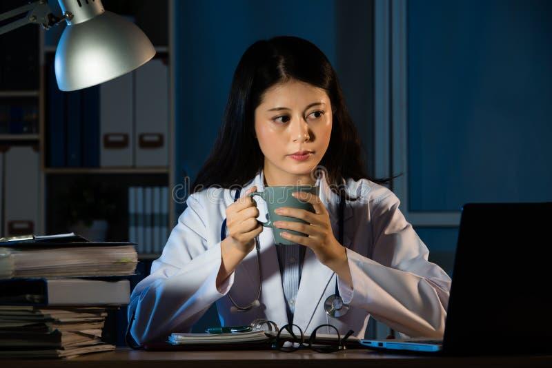 Doctor de la mujer que trabaja en el café de consumición de la noche imagenes de archivo