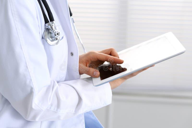 Doctor de la mujer usando la tableta blanca mientras que se sienta en la silla en el hospital, primer fotos de archivo
