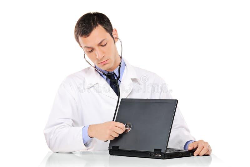 Doctor de la PC que examina un ordenador portátil foto de archivo libre de regalías