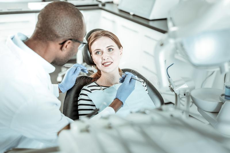 Doctor de piel morena que trabaja con su paciente bonito fotos de archivo