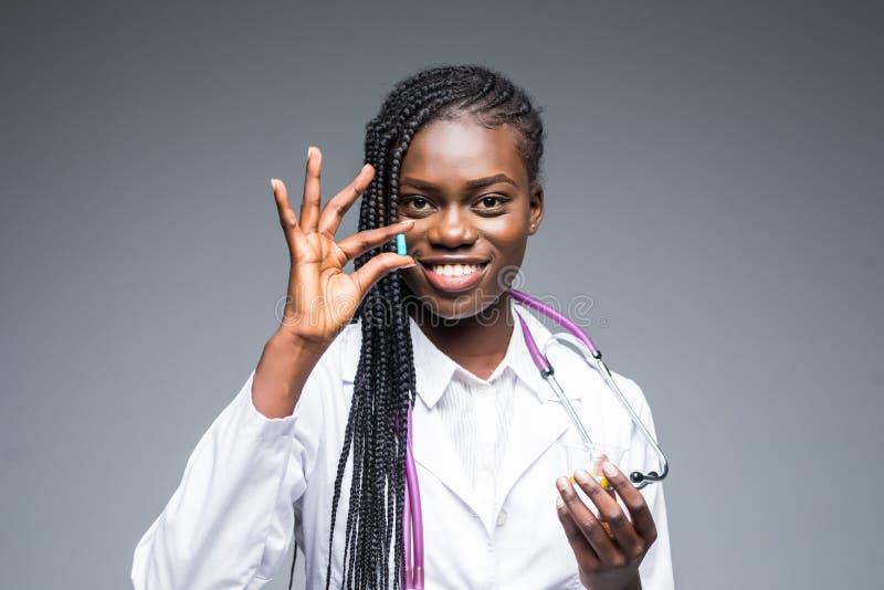 Doctor de sexo femenino africano de la mujer que soporta una curación de la droga del suplemento de la vitamina de la píldora ais foto de archivo libre de regalías