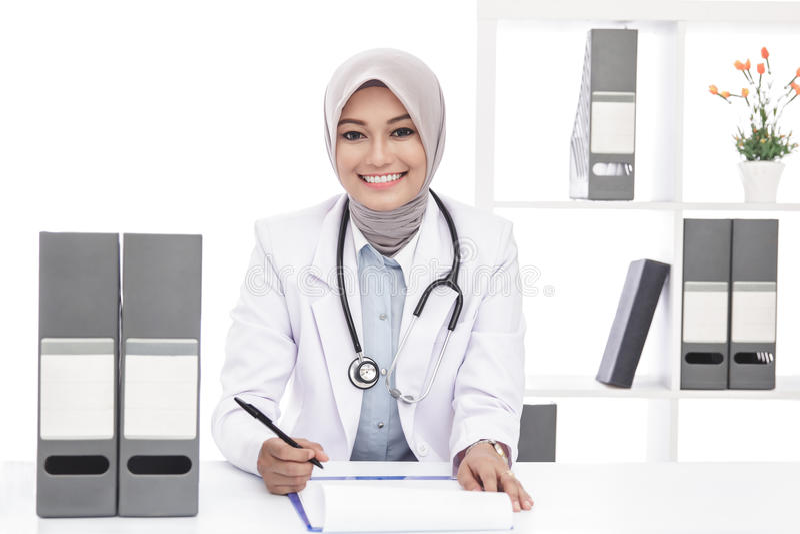 Doctor de sexo femenino asiático con el estetoscopio que sonríe mientras que anota fotografía de archivo