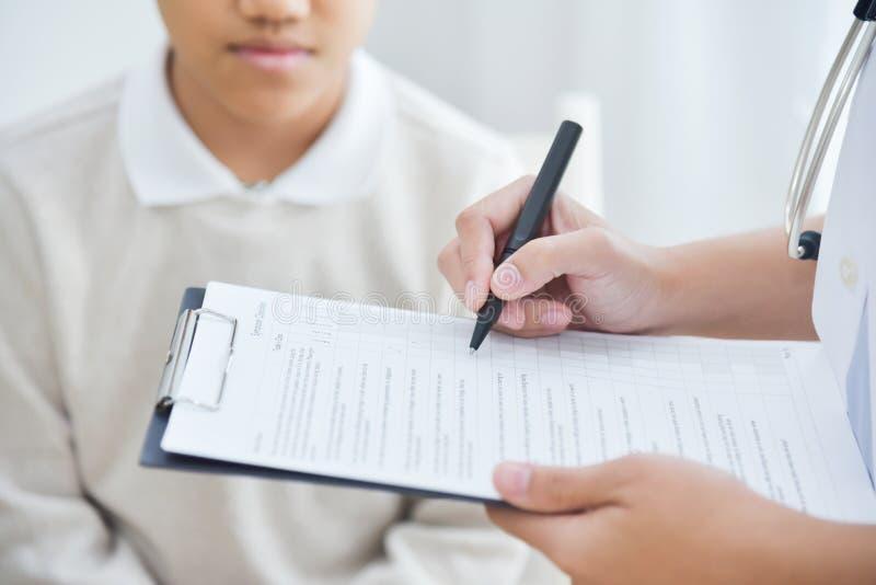 Doctor de sexo femenino asiático que toma la nota sobre la lista de control para un PA del niño pequeño imagen de archivo