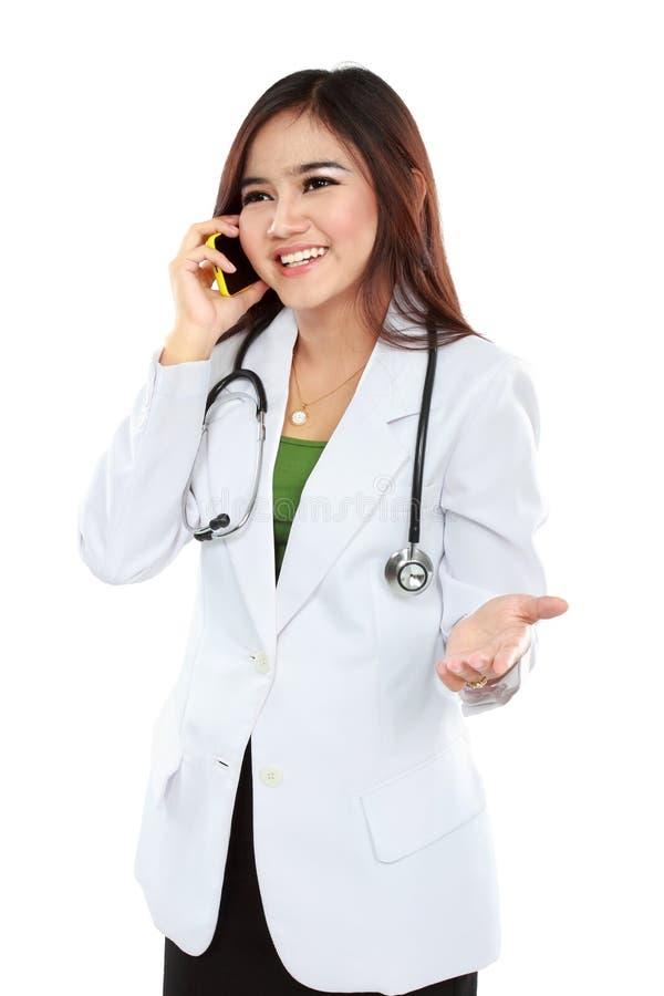 Doctor de sexo femenino atractivo en capa del laboratorio con el estetoscopio que habla los wi fotografía de archivo libre de regalías