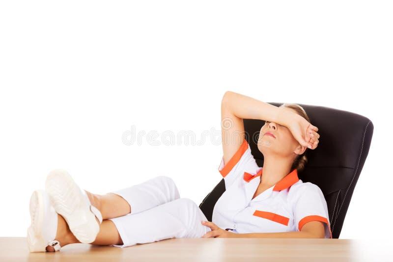Doctor de sexo femenino cansado joven que duerme con las piernas en el escritorio fotos de archivo