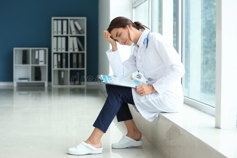 Doctor de sexo femenino cansado que se sienta en alféizar en su oficina fotos de archivo libres de regalías
