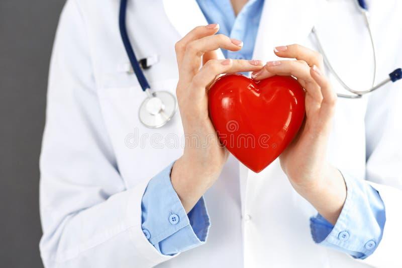 Doctor de sexo femenino con el estetoscopio que lleva a cabo el coraz?n en sus brazos Concepto de la atenci?n sanitaria y de la c foto de archivo libre de regalías