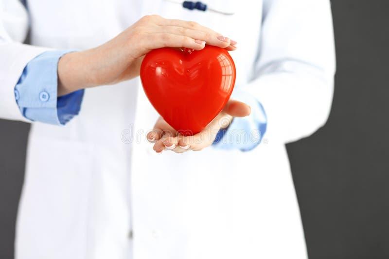 Doctor de sexo femenino con el estetoscopio que lleva a cabo el coraz?n en sus brazos Concepto de la atenci?n sanitaria y de la c fotografía de archivo