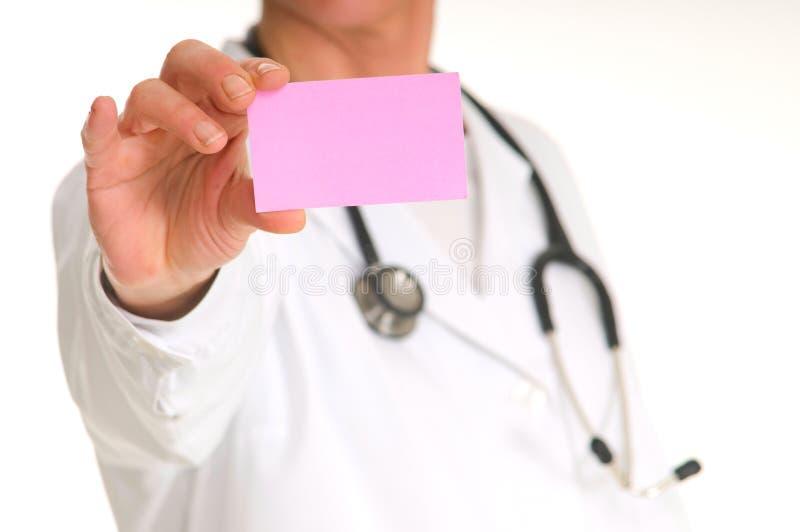 Doctor de sexo femenino con el estetoscopio que lleva a cabo una nota rosada imagen de archivo