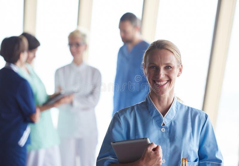 Doctor de sexo femenino con la tableta que se coloca delante del equipo fotos de archivo