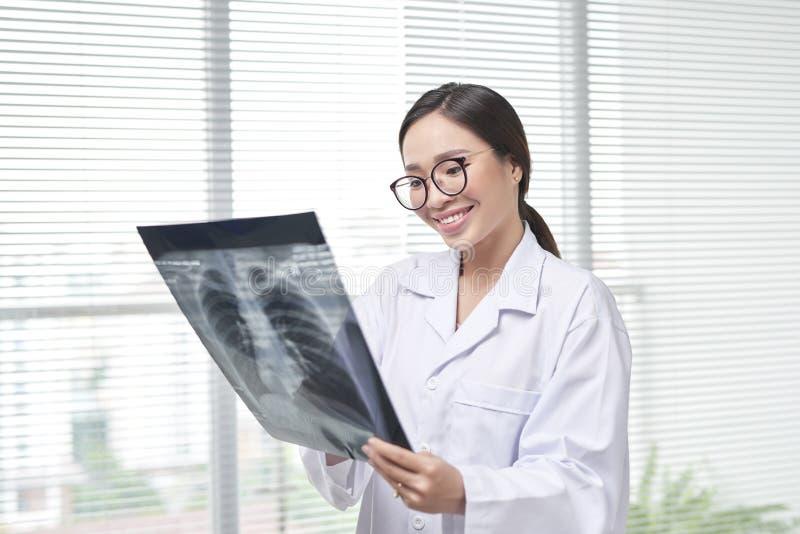 Doctor de sexo femenino confiado que examina exactamente una radiograf?a de la caja tor?cica foto de archivo