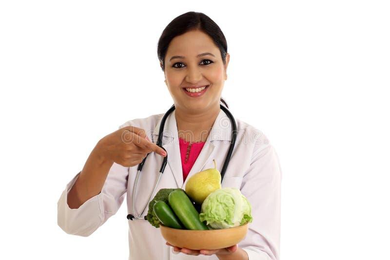 Doctor de sexo femenino del nutricionista que sostiene el cuenco de verduras imagenes de archivo