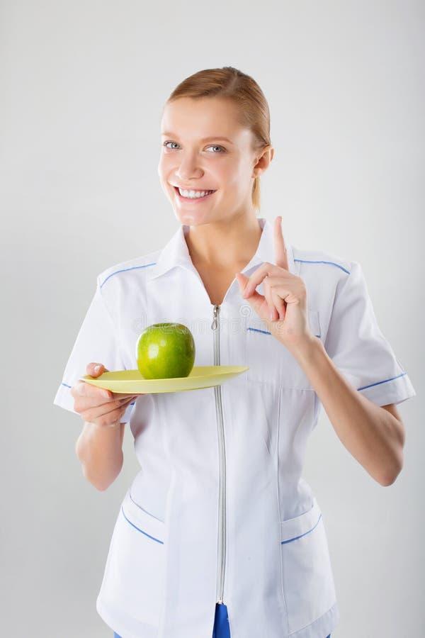 Doctor de sexo femenino del nutricionista que sostiene una manzana verde fotos de archivo