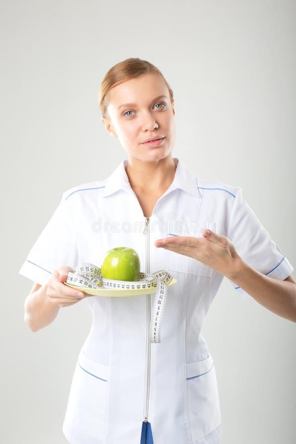 Doctor de sexo femenino del nutricionista que sostiene una manzana verde foto de archivo
