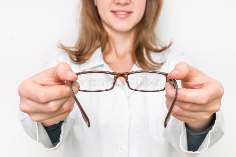 Doctor de sexo femenino del oculista que da los vidrios al paciente foto de archivo libre de regalías