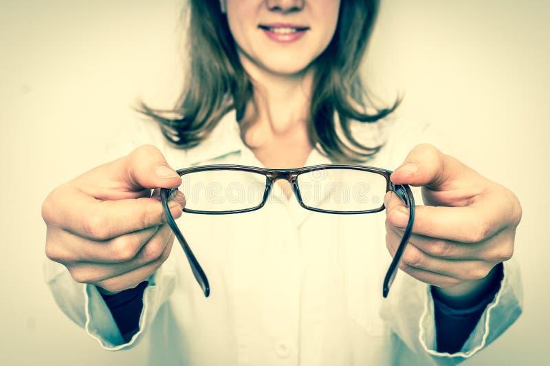 Doctor de sexo femenino del oculista que da los vidrios al paciente - estilo retro fotos de archivo libres de regalías