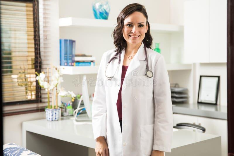 Doctor de sexo femenino delante de su oficina foto de archivo