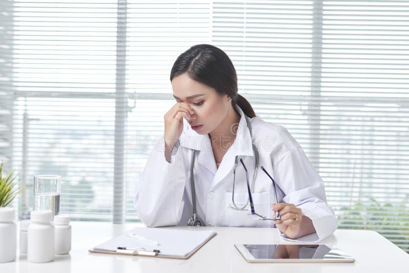 Doctor de sexo femenino desesperado que se sienta en su oficina fotografía de archivo