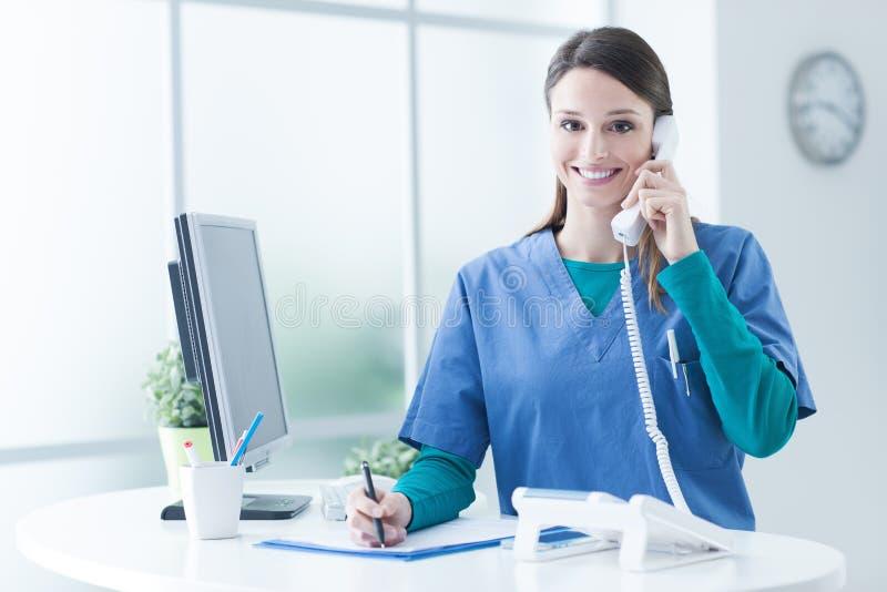 Doctor de sexo femenino en el mostrador de recepción imagen de archivo