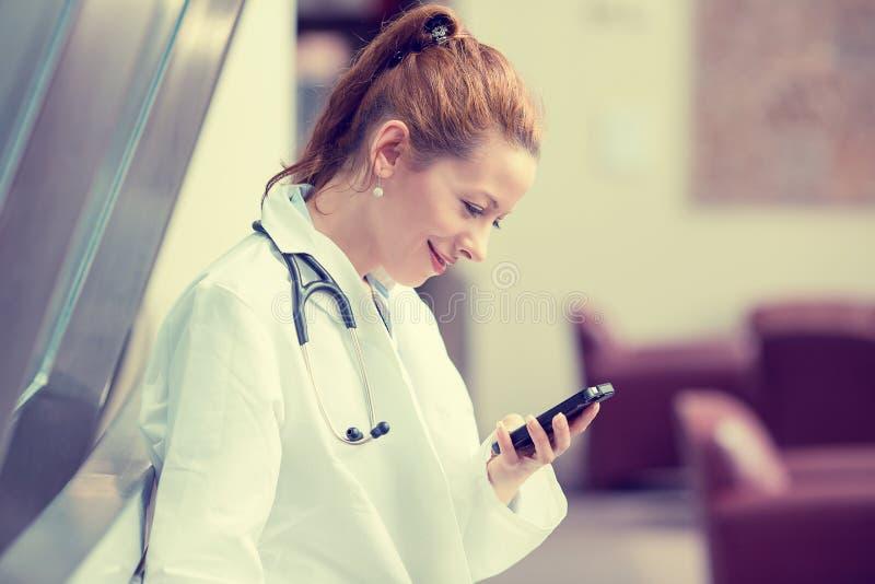 Doctor de sexo femenino en la capa blanca del laboratorio usando el teléfono elegante móvil imagen de archivo