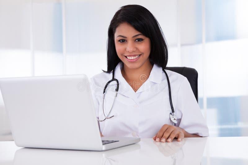 Doctor de sexo femenino feliz que usa el ordenador portátil foto de archivo