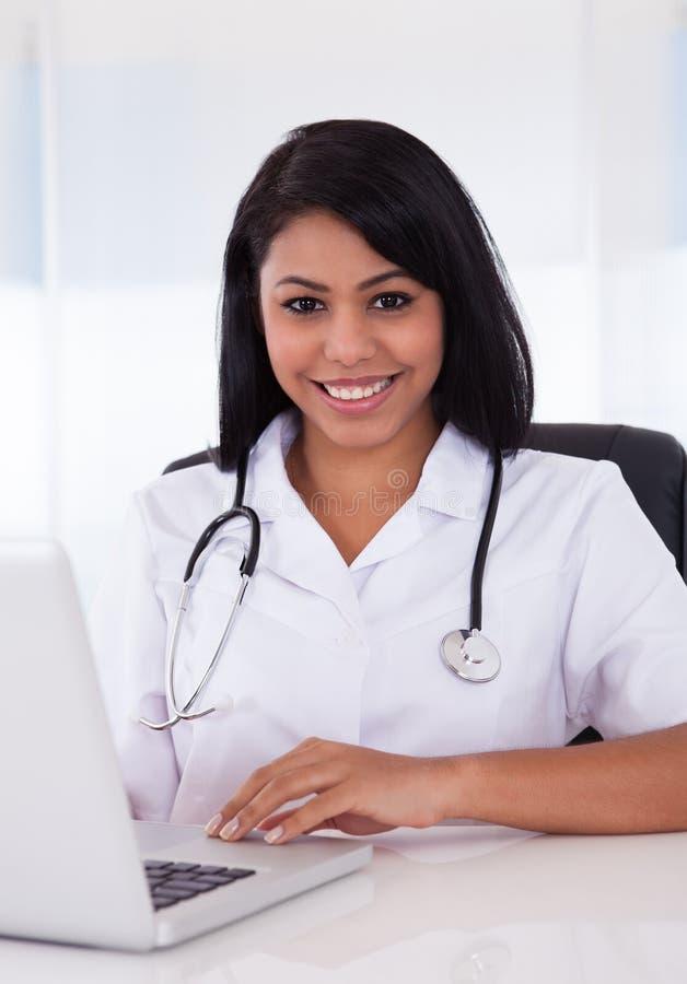 Doctor de sexo femenino feliz que usa el ordenador portátil fotografía de archivo libre de regalías