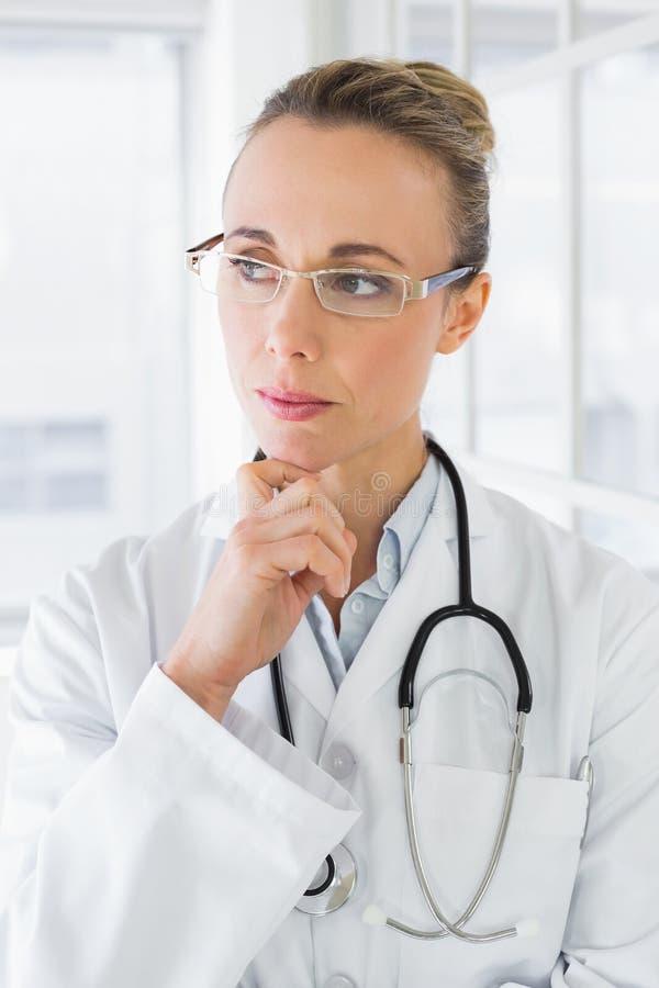 Doctor de sexo femenino hermoso contemplativo en hospital imágenes de archivo libres de regalías