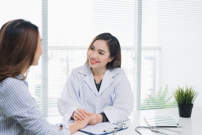 Doctor de sexo femenino hermoso en el doctor y el paciente médicos blancos de la capa fotos de archivo libres de regalías
