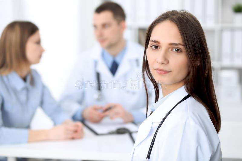 Doctor de sexo femenino hermoso joven que sonríe en el fondo con el paciente en hospital fotos de archivo