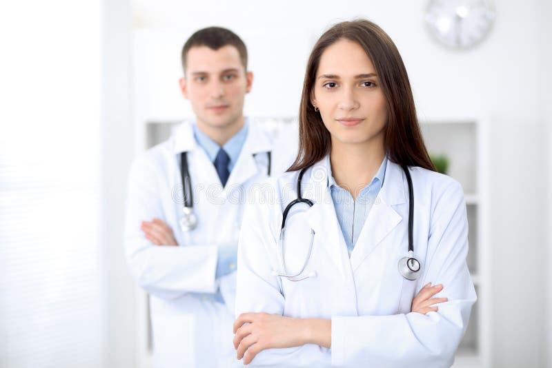 Doctor de sexo femenino hermoso joven que sonríe en el fondo con el paciente en hospital fotografía de archivo libre de regalías