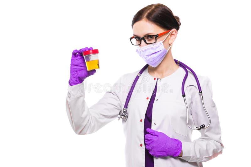 Doctor de sexo femenino hermoso joven que sostiene la muestra de orina en sus manos en máscara médica y los guantes estéril en el fotos de archivo libres de regalías