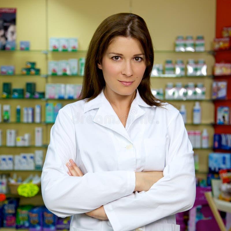 Doctor de sexo femenino hermoso que sonríe en farmacia fotos de archivo