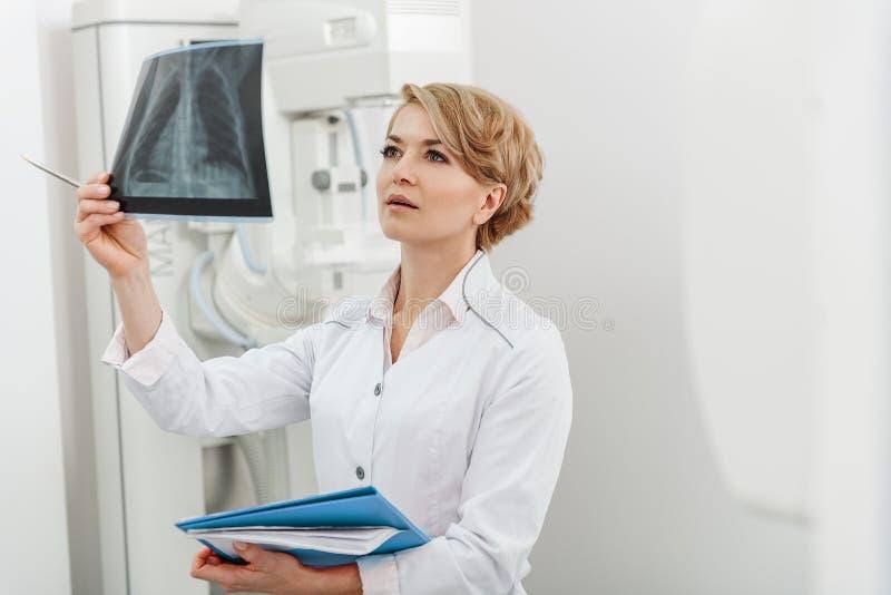 Doctor de sexo femenino interesado que sostiene la radiografía fotos de archivo