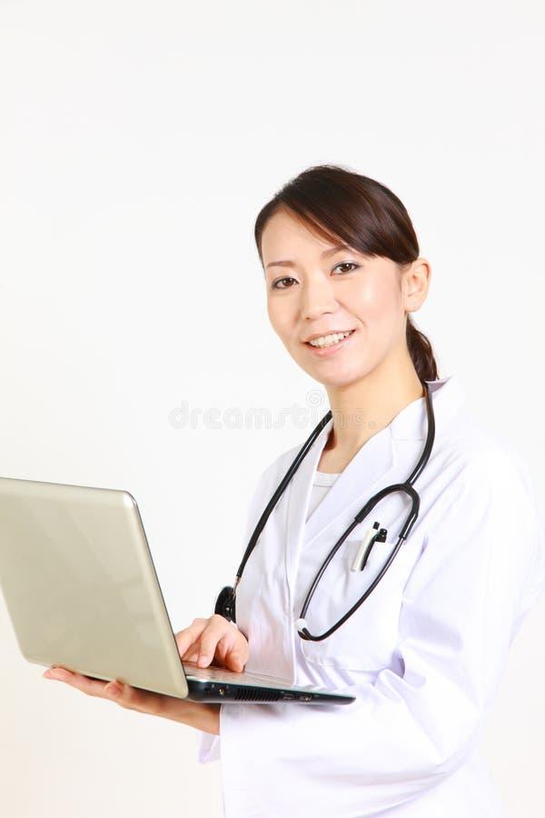 Doctor de sexo femenino japonés joven con sonrisas del ordenador portátil foto de archivo