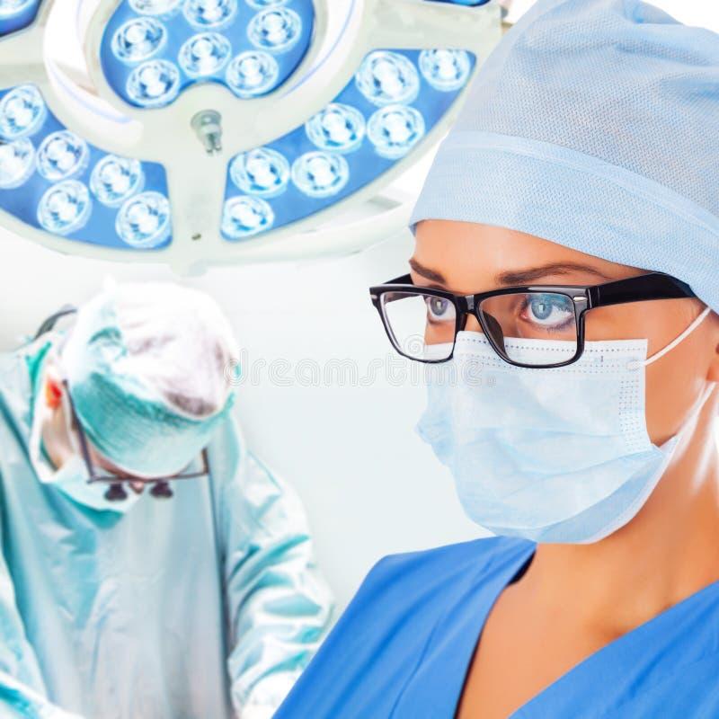 Doctor de sexo femenino joven con el cirujano en fondo fotos de archivo