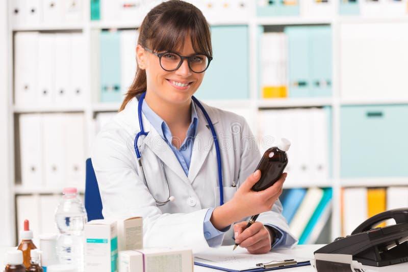 Doctor de sexo femenino joven de Smilng con la botella de la medicina fotos de archivo