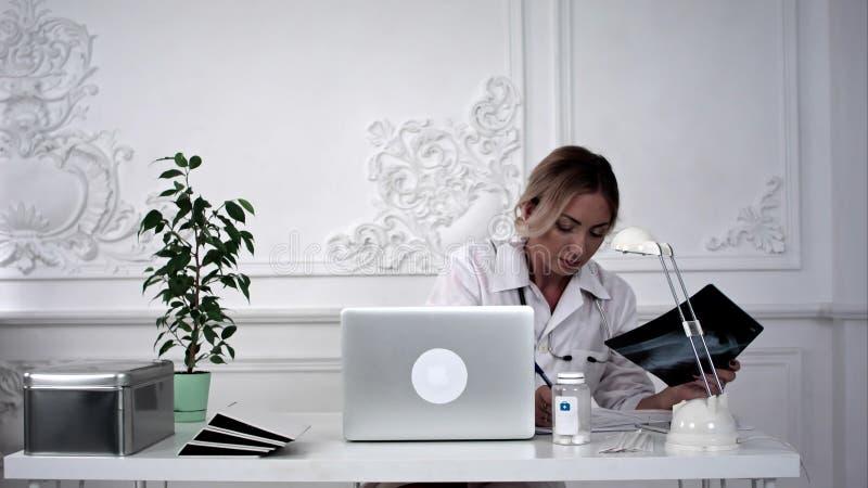 Doctor de sexo femenino joven que busca la foto de la radiografía y que hace notas imagen de archivo
