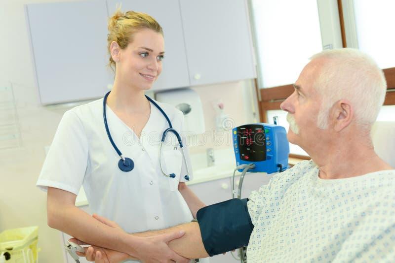 Doctor de sexo femenino joven que comprueba al paciente masculino mayor de la presión arterial fotos de archivo